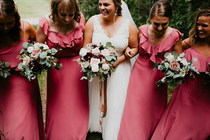 Bride and bridesmaids with pink berry coloured bridesmaid dresses holding bouquets featuring burgundy dahlias, keira garden roses, white ranunculus, amnesia roses, quicksand roses, blackberry scoop scabiosa, light pink astilbe and eucalyptus greenery.