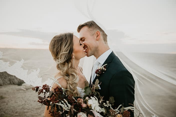 bride and groom kissing under her veil with bride holding an ivory and burgundy floral bouquet