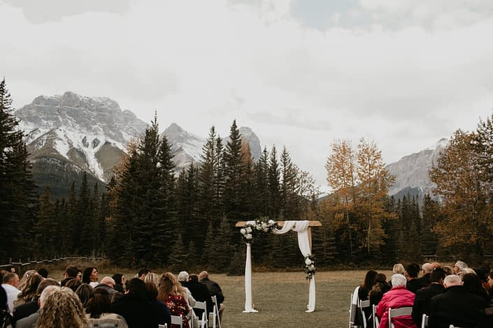 Canmore outdoor ceremony archway draped with white linens with white hydrangea flower arrangements