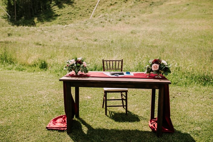 Rustic Chic Burgundy and Blush Wedding signing table decorated with fresh floral arrangements of burgundy dahlias, white o'hara garden roses, black baccara roses, quicksand roses and eucalyptus is gold mercury glass compote vases.