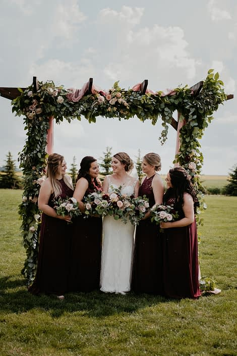 Crystal's bridesmaids standing under a wooden archway covered in a fresh greenery garland adorned with flowers including burgundy dahlias, cappuccino roses, quicksand roses, and astilbe.