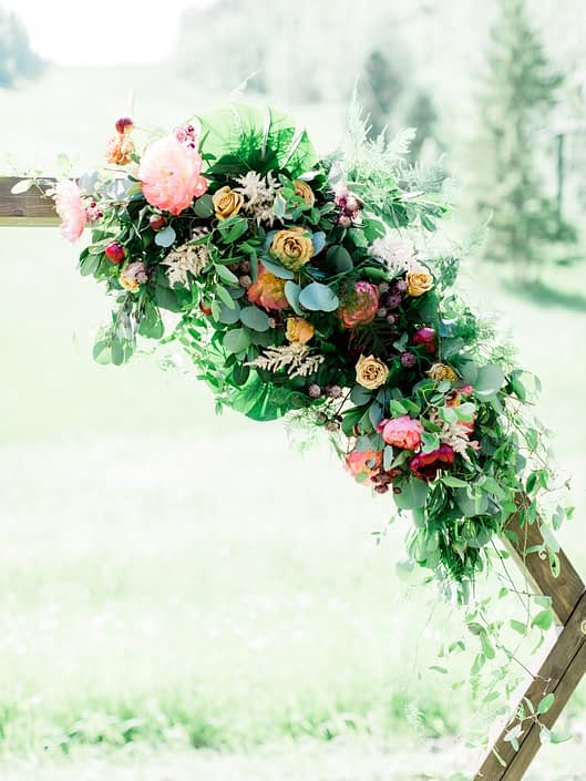 Modern Coral Charm Peony arrangement on a wooden hexagon arch featuring coral charm peonies, golden mustard roses, cappuccino roses, burgundy dahlias, astrantia, astilbe, plumosa, monstera leaves, and eucalyptus greenery.