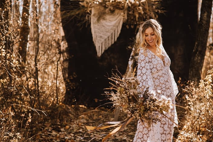 Blonde boho bride in crochet dress in the fall in the woods with dried pampas grass back drop with crochet and bouquet of foraged dried flowers