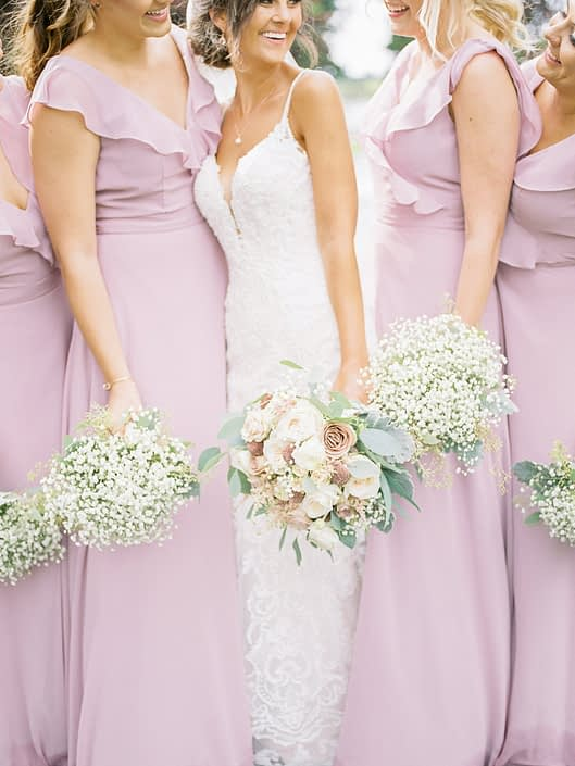 Bride and bridesmaids holding bouquets; bridal bouquet featuring rose gold painted scabiosa pods, blush white o'hara garden roses, dusty pink quicksand and amnesia roses, astilbe, white ranunculus, babies breath, dusty miller and eucalyptus; bridesmaids wearing dusty rose pink dresses and holding white babies breath bouquets.
