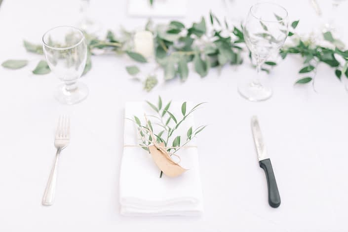 Timeless white wedding place setting, folded linen napkin with fresh italian ruscus, twine and name tag.
