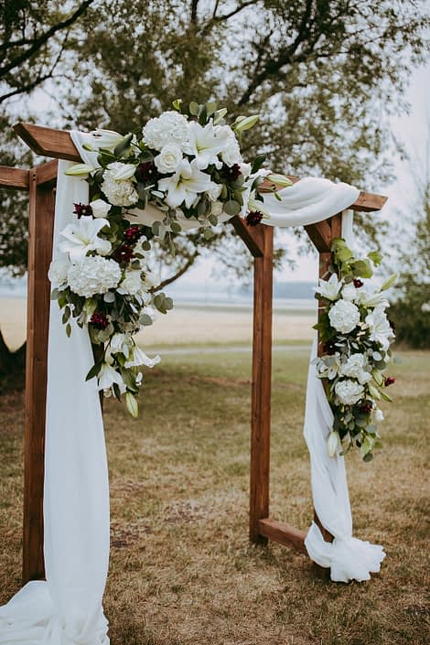 rustic archway with white voile and flower arrangements made with white hydragea and white lilies and roses and burgundy dahlia