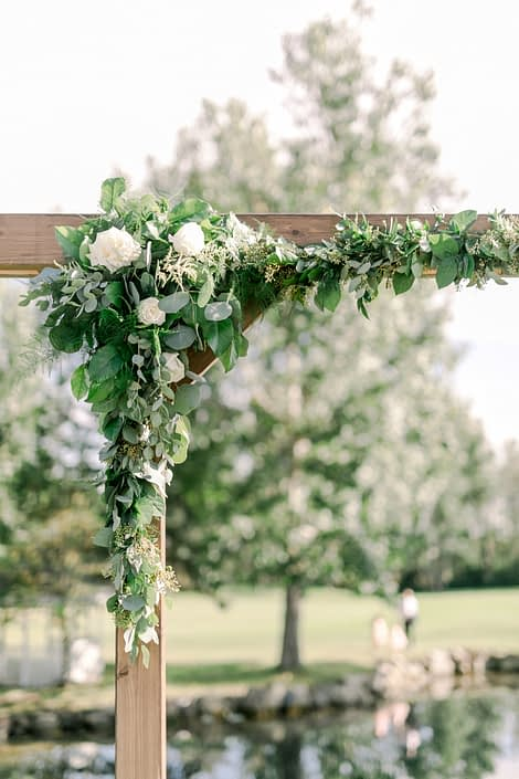 Corner archway arrangement on a wooden archway designed with white Tibet roses, a mixed variety of eucalyptus, italian ruscus, salal and plumosa.