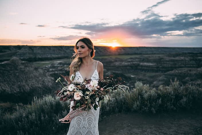 sunset photoshoot in drumheller with bride holding a boho sytle bridal bouquet designed with roses, scabiosa, and amaranthus with silk trailing ribbons
