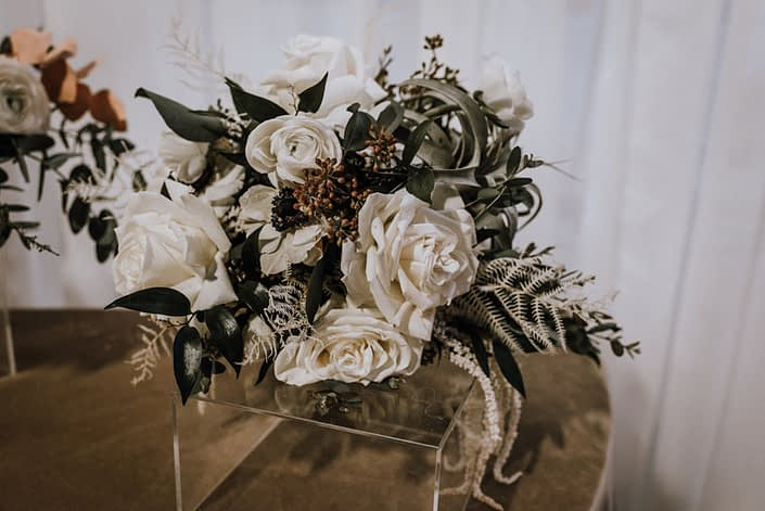 An arrangement designed with an air plant, ivory roses, white hanging amaranthus, and eucalyptus greenery.
