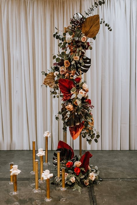 Cambridge Bridal Show 2020 - dramatic tall vertical arrangement made of black monstera leaves, red and metallic dyed Anahaw palm leaves, red and blush roses, and eucalyptus greenery.