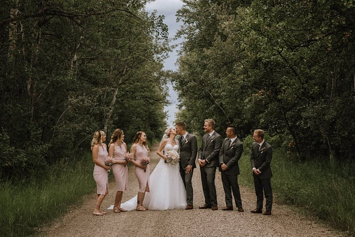 wedding party in blush and charcoal grey holding bouquets made with astilbe and white hydrangea
