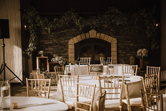 Canyon Ski Resort wedding with white linens and gold chiavari chairs with fresh eucalyptus garland to decorate the fireplace mantle