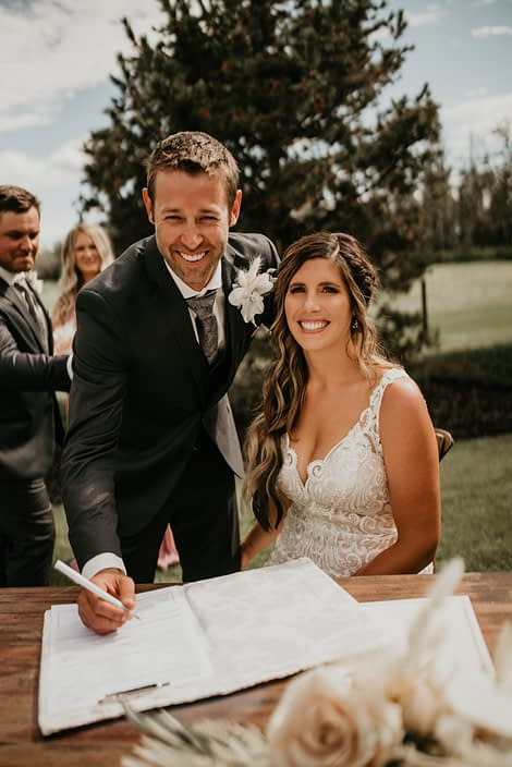 Bride and groom signing table with phalaenopsis orchid boutonniere accented by bunny tail, astilbe and bleached bracken fern