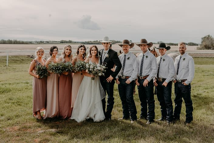 Erika and Colt's Blush and Mauve Country Wedding bridal party. The bridesmaids are wearing mauve floor length dresses carrying eucalyptus bouquets, the groom and groomsmen are wearing cowboy hats and boutonnieres and the bride is wearing a white dress and carrying a white, ivory and blush bouquet.