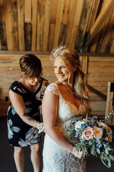 Kelsie and her mom doing up her bridal gown and holding her blush and blue bridal bouquet featuring white o'hara garden roses, quicksand roses, delphinium, gypsophila, and a mixed variety of eucalyptus greenery.