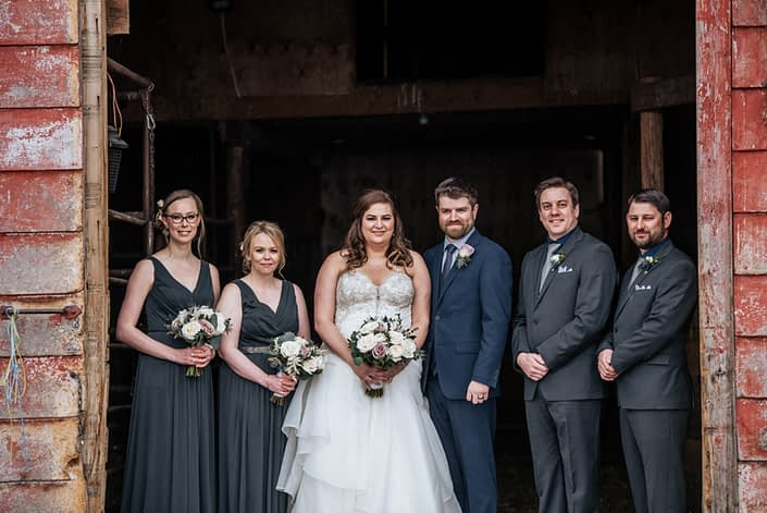 Mauve and Navy Bridal party; bridesmaids wearing charcoal grey dresses and carrying mauve and ivory bouquets designed with roses, ranunculus and eryngium; bride with mauve and ivory bouquet accented by blue and groom and groomsmen with boutonnieres