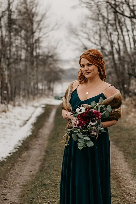 Rustic Boho Chic Wedding - Bridesmaid wearing emerald green dress and fur shawl off the shoulders while holding a bouquet made of red peony, blush and pink roses, and eucalyptus greenery.