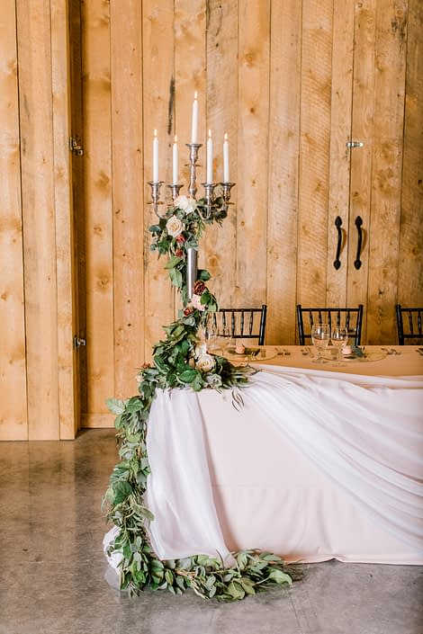 Head table tall candlestick holder decor with fresh greenery garland accented by blush and burgundy florals