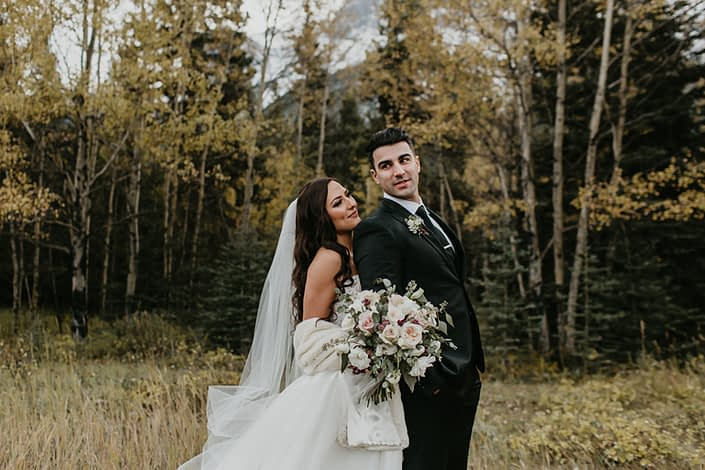 Brittany and Briggs with ivory and blush bridal bouquet designed with quicksand roses, white o'hara garden roses, white ranunculus, white lisianthus, burgundy astrantia, and eucalyptus greenery
