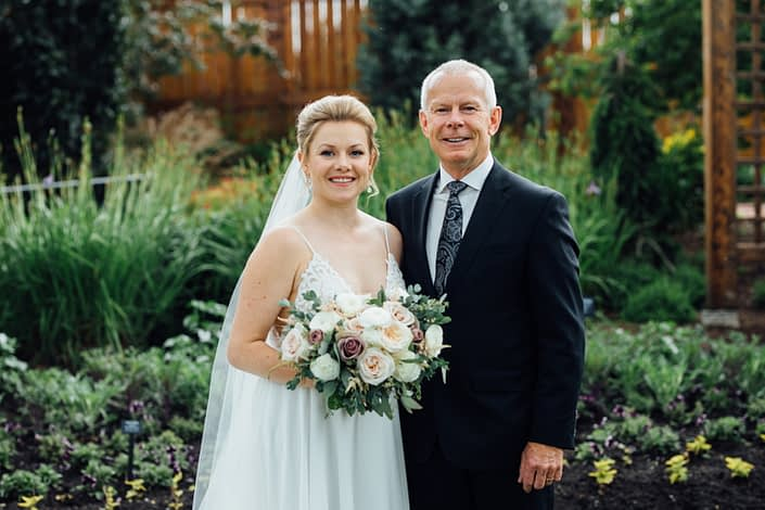 Bride and father standing together with romantic blush bridal bouquet designed with white o'hara garden roses, quicksand roses, white ranunculus, light pink astilbe, and eucalyptus greenery.