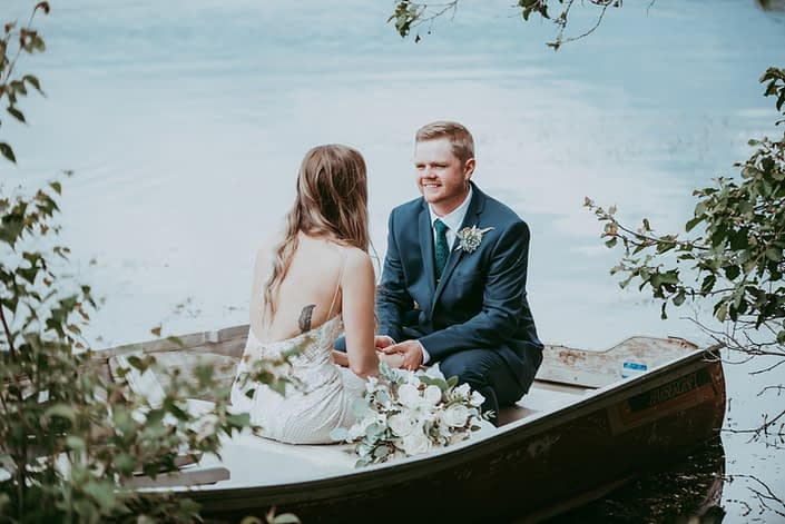 Bride and groom looking at each other in a boat with white bridal bouquet