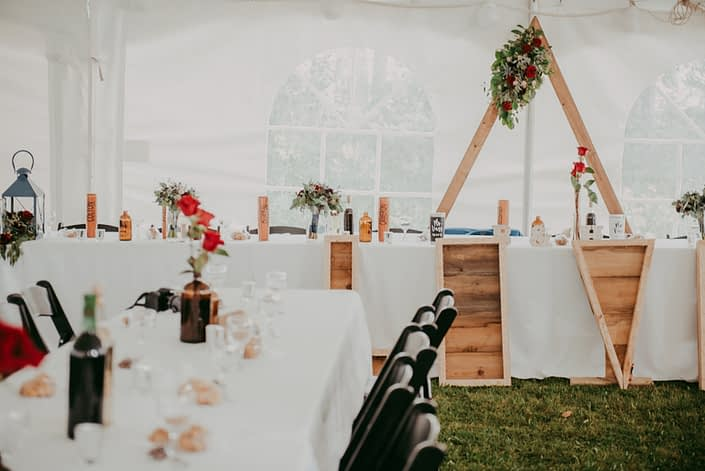 Reception for burgundy and royal blue wedding in a tent; head table with triangle archway flower arrangement and black bacarra red roses in brown bottles