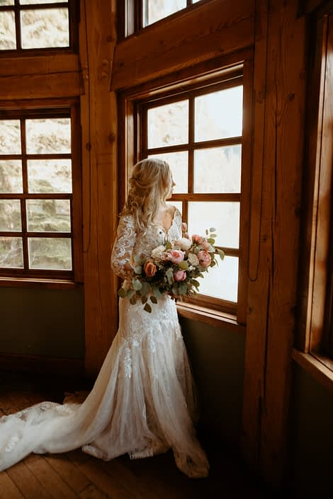 Bride standing next to window in Emerald Lake Lodge with bouquet of peonies, roses, tulips and eryngium