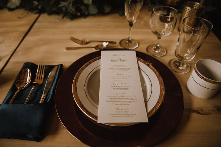 Elegant table setting with teal napkin and menu card on a gold charger