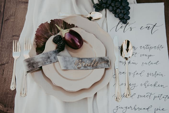 Place setting at harvest autumn table with grapes and aubergine and velvet placecards for bride with gold cutlery and beige dinnerware on blush silk tablerunner