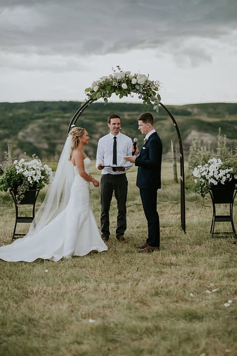 Bride and groom, Brooke and Levi, standing under an archway adorned with a flower arrangement made of white hydrangea, white o'hara garden roses, playa blanca roses, quicksand roses, salal, Italian ruscus and eucalyptus greenery.