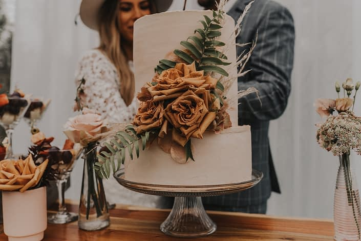 Modern boho and terracotta styled shoot cake decorated with fern, grasses and toffee roses