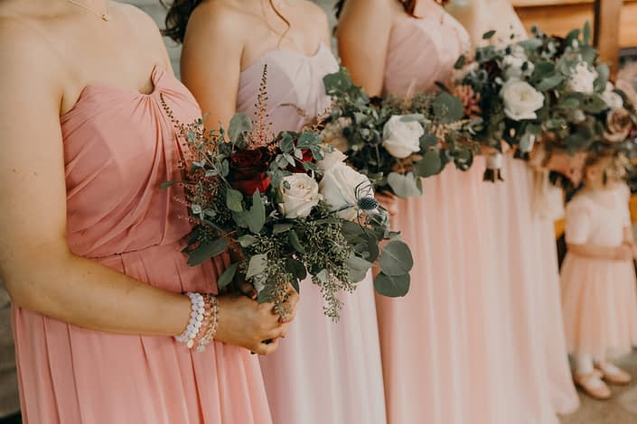 blush wedding party with bouquets made with quicksand roses and white o'hara garden roses and red roses and pink astilbe and eryngium and eucalyptus