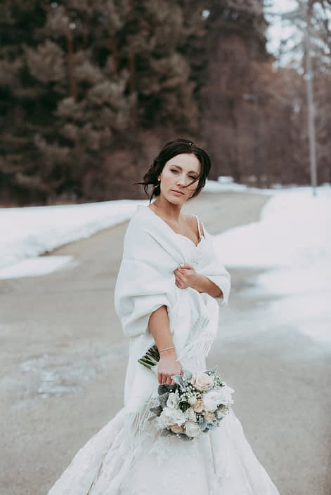 Bride in winter with a white shawl and bridal bouquet of white peony and ivory roses
