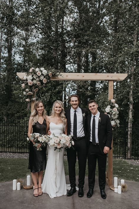 Bride and bridesmaids with pastel bouquets under a wooden archway decorated with floral arrangements of roses, poppies, peonies, ranunculus and greenery