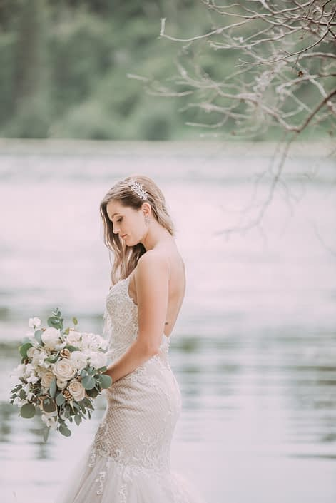 Bride standing beside a lake with a white bouquet made of roses, ranunculus, sweet peas and eucalyptus
