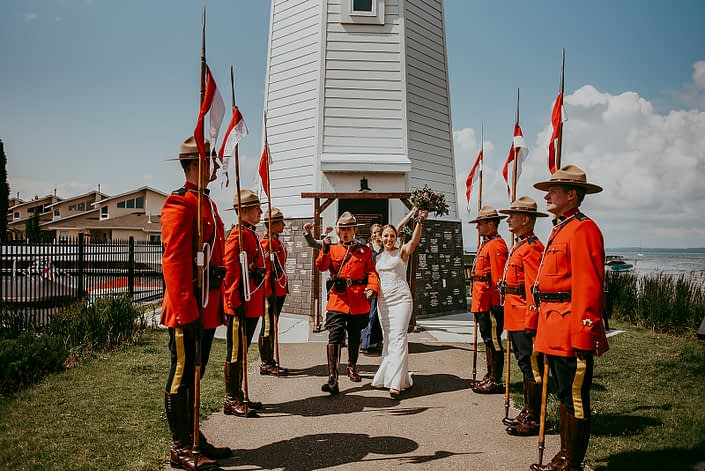 Sean and Tanya's RCMP wedding after the ceremony - bride holding bouquet designed with burgundy and navy flowers and eucalyptus