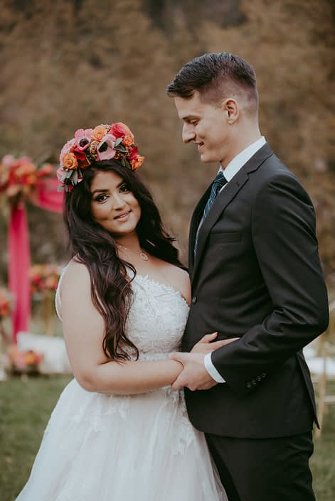 Bride and groom with colourful fuchsia and orange flower crown made of anemones, zinnias, and roses
