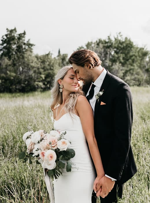 Bride and groom with pastel bouquet in a field