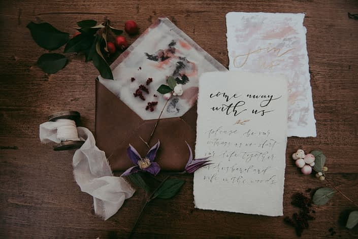 Detail photo of an wedding invitation suite with pueple clematis, blush snowberry and red berries