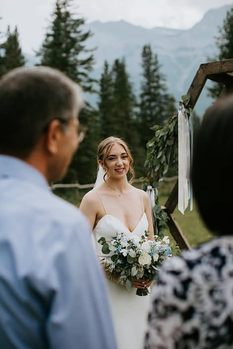 Bride with white and blue bouquet at ceremony