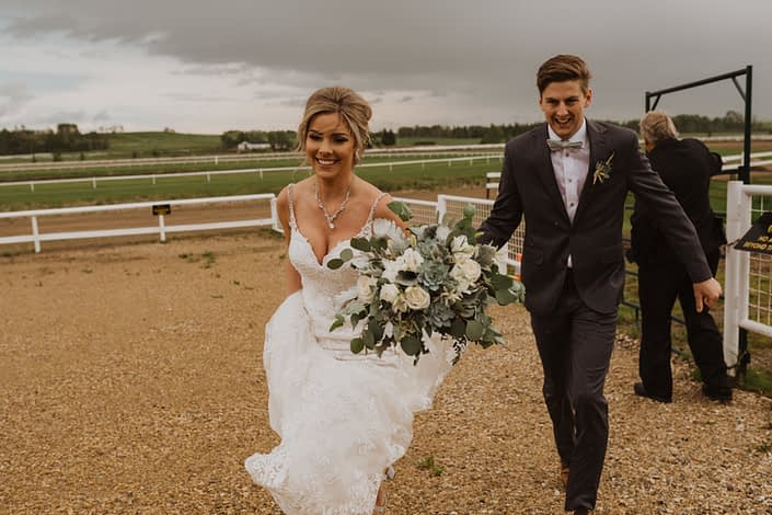 Bride and groom with a white and grey green bridal bouquet made of Playa Blanca roses, lisianthus, astilbe, blue star succulents, dusty miller and a variety of eucalyptus greenery.