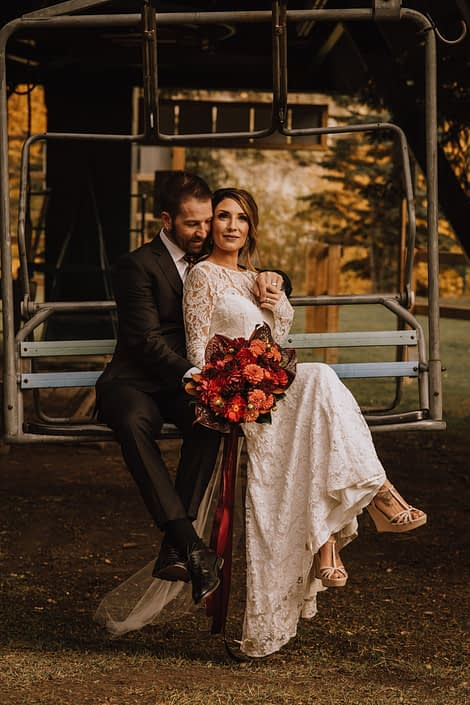 bride and groom on ski lift with lace dress in fall and bouquet with orange dahlia and red roses and red dahlia and burgundy anthurium and magnolia leaves and trailing ribbons