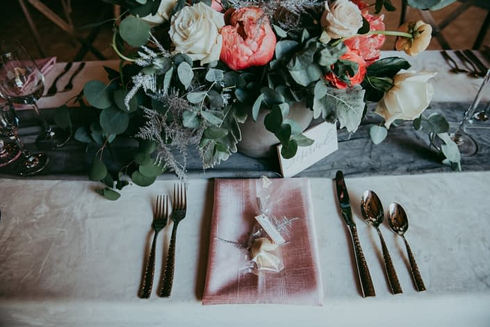 Tablescape for Canyon Ski Resort Open House 2019; ivory velvet tablecloth, blush napkin, fortune cookie, silver lucca flatware, smoked grey velvet table runner, and a coral and blush floral arrangement in a concrete vase designed with coral charm peonies, quicksand roses, playa blanca roses, peach ranunculus, silver plumosa, and a mixed variety of eucalyptus greenery.