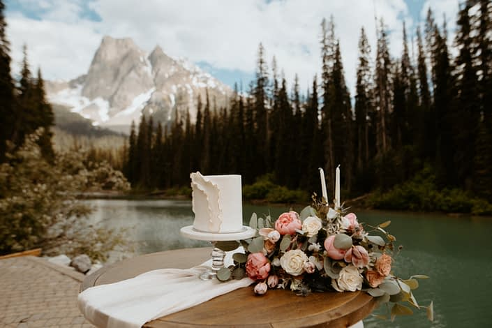 Cake Table with a view of Emerald Lake and the Rocky mountains; white ruffled wedding cake and blush pink and white bridal bouquet designed with roses, peonies and tulips