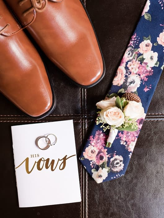 Groom's tie, shoes, boutonniere, vows and rings flat lay.