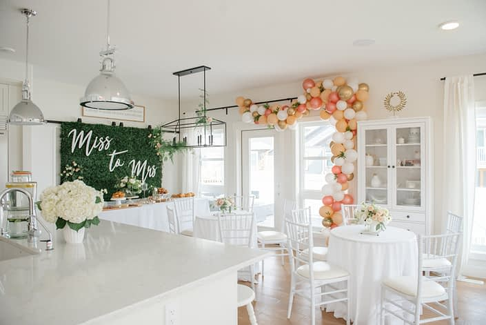 Bridal shower in white house with ocktail table arrangements and boxwood backdrop and balloon garland in blush, peach and gold with hydrangea flower arrangements