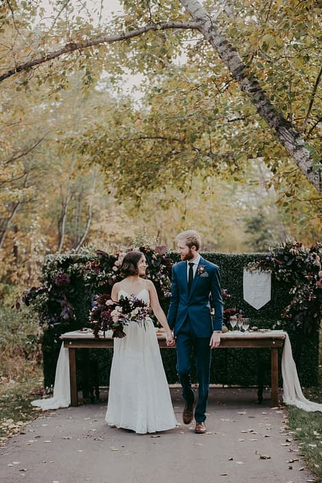 Bride and Groom in front of harvest table in the fall at Mckenzie trails with florals in burgundy and blush