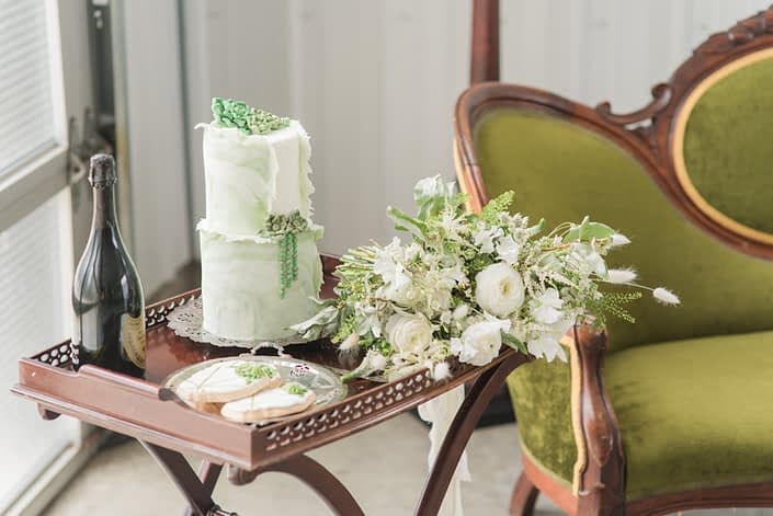 Drink cart covered with champage, cake, and green and white bridal bouquet featuring poppies, ranunculus, veronica, astilbe, sweet peas, bunny tails, wax flower and greenery.