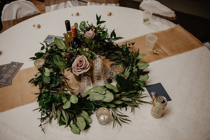 Rustic Boho Chic Wedding - Greenery wreath garland centrepiece made of salal, eucalyptus, italian ruscus, and mauve roses. The table is covered in ivory linens and a burlap table runner.