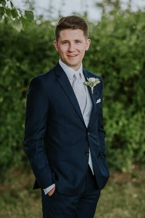 Levi wearing a classic white ranunculus boutonniere accented by eucalyptus greenery.